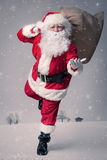 Santa Claus running. With the bag of the presents Royalty Free Stock Photos