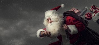 Santa Claus running and delivering gifts Royalty Free Stock Images