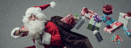 Santa Claus running and delivering gifts. Santa Claus running and delivering Christmas presents: he is late and losing gifts from his sack stock image