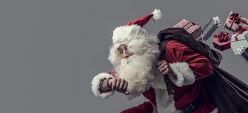 Santa Claus running and delivering gifts stock photo