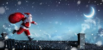 Santa Claus Running On The Rooftops Stock Afbeelding