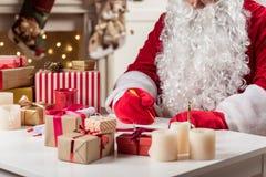 Santa Claus sérieuse faisant des notes au bureau Image stock