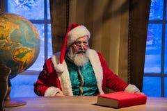Santa Claus s'asseyant dans sa chaise à son bureau Images stock