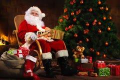 Santa Claus s'asseyant devant la cheminée Images libres de droits