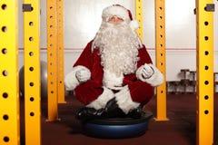 Santa Claus s'asseyant en position de yoga dans le gymnase Image libre de droits
