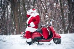 Santa Claus s'asseyant sur le scooter rouge photographie stock libre de droits