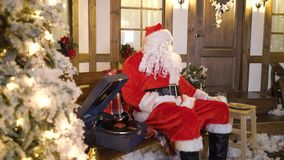 Santa Claus s'assied près de la maison entre les arbres de Noël, boissons traient, mangent des biscuits, écoute des chansons de N banque de vidéos