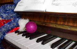 Santa Claus's cap and Christmas decorations lie on a piano. Royalty Free Stock Photos
