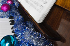 Santa Claus's cap and Christmas decorations lie on a piano. Royalty Free Stock Photography