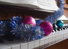 Santa Claus's cap and Christmas decorations lie on a piano. Royalty Free Stock Images