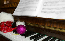 Santa Claus's cap and Christmas decorations lie on a piano. Royalty Free Stock Image