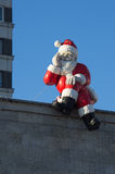 Santa Claus's figure. The thoughtful Santa Claus's figure sitting on the rooftop against the background of the blue sky Royalty Free Stock Photography