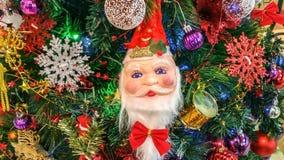 Santa Claus & x27; s-framsida på en julgran och prydnader Arkivbild