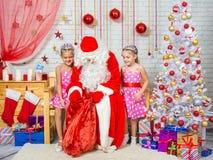 Santa Claus saca un bolso de regalos a dos muchachas Imagen de archivo