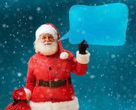 Santa Claus with sack of gifts showing sign speech bubble banner, looking happy excited. Stock Photos