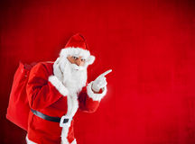 Santa Claus with sack pointing in blank red Royalty Free Stock Photography