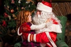 Santa Claus sammanträde i en stol med lite flickan Arkivbild