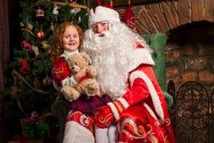 Santa Claus sammanträde i en stol med lite flickan Arkivfoton