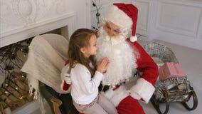Santa Claus sammanträde i en stol med lite flickan som drömmer om hennes julklappar Fotografering för Bildbyråer
