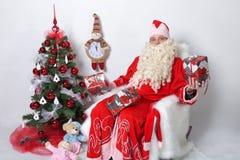 Santa Claus sammanträde med gåvor på julgranen På en vit bakgrund Royaltyfri Fotografi