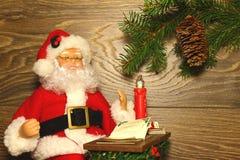 Santa Claus sammanträde på tabellen Royaltyfri Foto