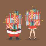 Santa claus and Santa woman holding a pile of gift boxes Stock Photo