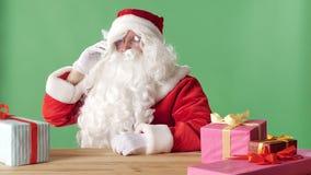 Santa Claus satisfeita fala no telefone, ri, senta-se na tabela com presentes, chromakey verde no fundo vídeos de arquivo