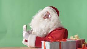 Santa Claus satisfeita guarda dólares, dinheiro, e mostra um sinal de gosto, chromakey no fundo video estoque