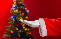 Santa Claus se abre la mano con el árbol de navidad adornado encendido detrás Foto de archivo libre de regalías