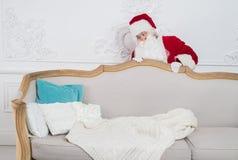 Santa Claus se cachant derrière un sofa au-dessus de l'intérieur à la maison Photographie stock