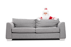 Santa Claus se cachant derrière un sofa Photos stock