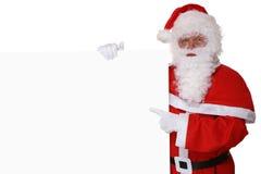 Santa Claus se dirigeant avec le doigt sur Noël à la bannière vide Photographie stock libre de droits
