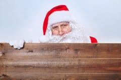 Santa Claus se dirigeant dans la bannière en bois de publicité de blanc avec l'espace de copie photo libre de droits
