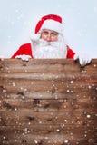 Santa Claus se dirigeant dans la bannière en bois de publicité de blanc avec l'espace de copie images stock