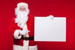 Santa Claus se dirigeant dans la bannière vide de publicité d'isolement sur le fond rouge avec l'espace de copie Photos stock