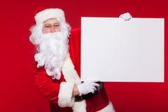 Santa Claus se dirigeant dans la bannière vide de publicité d'isolement sur le fond rouge avec l'espace de copie Photo stock