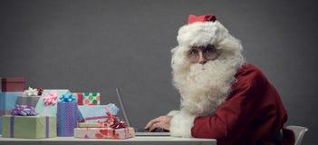 Santa Claus se reliant à son ordinateur portable image stock