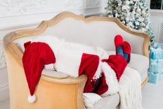 Santa Claus se reposant sur un sofa à la maison Photos libres de droits