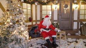 Santa Claus se sienta cerca de la casa entre los árboles de navidad, bebidas ordeña, come las galletas, escucha las canciones de  almacen de metraje de vídeo