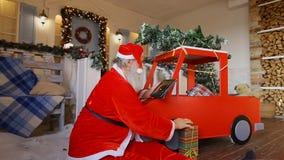 Santa Claus se sienta en el centro del piso del sitio y termina para hacer los regalos para los niños almacen de video