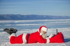Santa Claus se trouvant sur la neige, regardant des actualités d'ordinateur portable Photos libres de droits