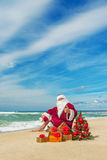 Santa Claus at sea beach with many gifts and decorated christmas Royalty Free Stock Images
