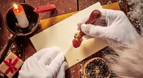 Santa Claus sealing an envelope with a decorative red wax seal showing his face in a close up of his hands lit by candlelight.  royalty free stock photos