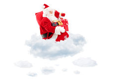 Santa Claus seated on clouds holding a bag and presents Stock Images