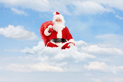 Santa Claus seated on clouds holding a bag Stock Photography