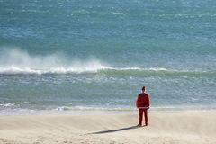 Santa claus on the beach. Santa claus, seen from behind, standing on the beach facing the horizon royalty free stock photo