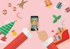 Santa Claus sending gift using smartphone with decorations and g royalty free stock image