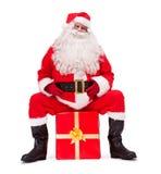 Santa Claus senta-se em uma caixa de Natal Fotografia de Stock Royalty Free