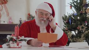 Santa Claus talking on phone. Santa Claus with serious face in red costume near bright decorated fir tree and fireplace talking on the cell phone. Old man is stock footage