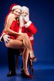 Santa Claus with sexy girl in Santa hat. Royalty Free Stock Photography
